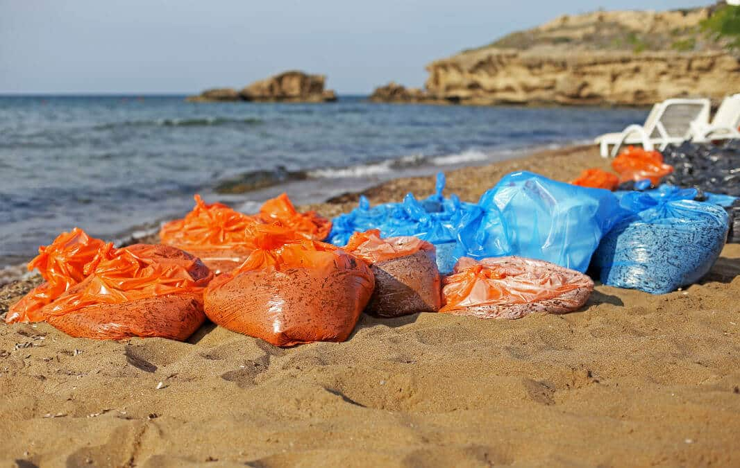 orange and blue plastic bags on the sand by the sea